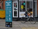 """A youth cycles past a sign telling local residents to """"Social Distance"""" and advising on how to help """"Prevent the Spread"""" of coronavirus, in the North Evington district of Leicester, central England, on June 29, 2020. - The central English city of Leicester could be the country's first to face a local lockdown due to a rise in coronavirus cases, the UK's Home Secretary Priti Patel said on June 28. The Midlands city recorded 658 new cases in the two weeks up to June 16, many linked to fresh outbreaks at food production plants. (Photo by Ben STANSALL / AFP)"""