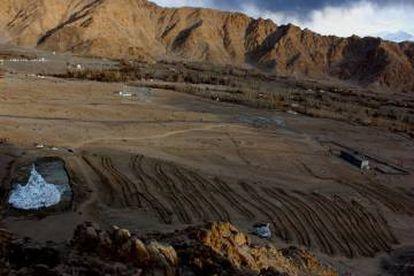 À esquerda, destaca-se uma estupa de gelo em plena paisagem desértica