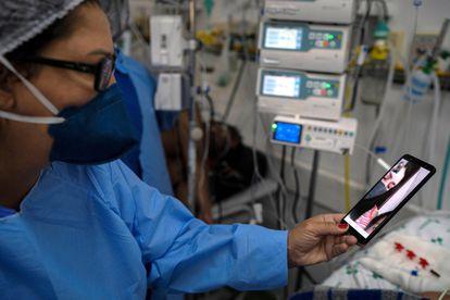 Enfermeira ajuda fazer uma video chamada entre um paciente com covid-19 e um parente na cidade de São Leopoldo, no Rio Grande do Sul.
