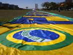 A large Brazilian flag lays in the Ministries Esplanade during a rally by supporters of Brazilian President Jair Bolsonaro in support of loosened gun control Brasilia, Brazil, Friday, July 9, 2021. (AP Photo/Eraldo Peres)