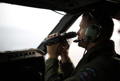 Um piloto da força aérea da Nova Zelândia busca restos do MH370.