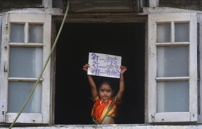 "Menina indiana segura cartaz onde se lê ""Ninguém deve sair de casa"", em Mumbai."