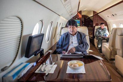 Evo Morales folheia os jornais, na última terça-feira, no avião presidencial.