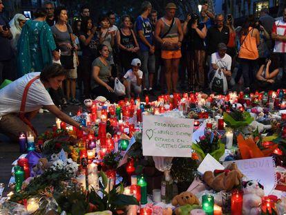 Pessoas deixam flores e velas em homenagens às vítimas em Las Ramblas.