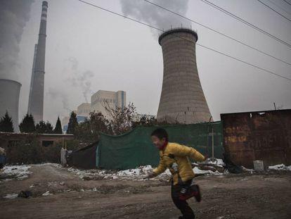 Um menino corre perto de uma central térmica de carvão em Pequim (China).