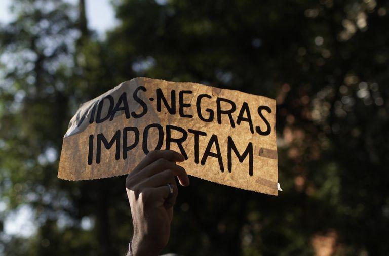 """Manifestantes se unem ao grito de ordem, agora global: """"vidas negras importam""""."""