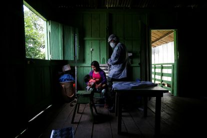 Integrante da equipe médica das Forças Armada examina mulher Yanomami.