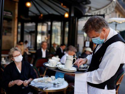 Garçom atende clientes em um café de Paris.
