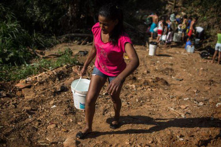 Mulher recolhe água com um balde, em Itu.