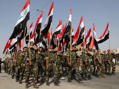 Voluntários xiitas participam em um desfile em Bagdá.