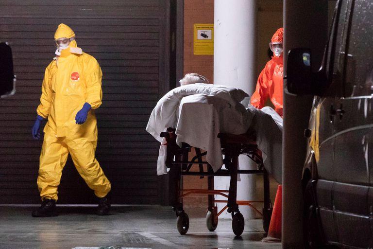 Enfermeiros do serviço de saúde de Múrcia, na Espanha, transferem um homem de uma casa de repouso para o hospital.