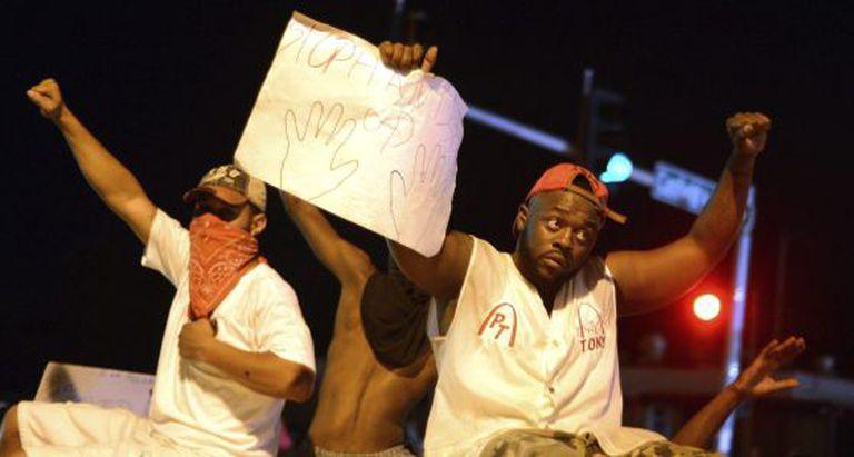 Manifestantes protestam no local onde morreu Michael Brown.