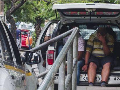 Presos são algemados em veículos policiais por falta de vaga em presídios.