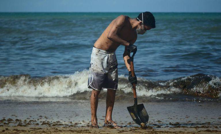 Jovem retira na terça-feira o óleo que atingiu praia de Itapuama, no litoral sul de Pernambuco.