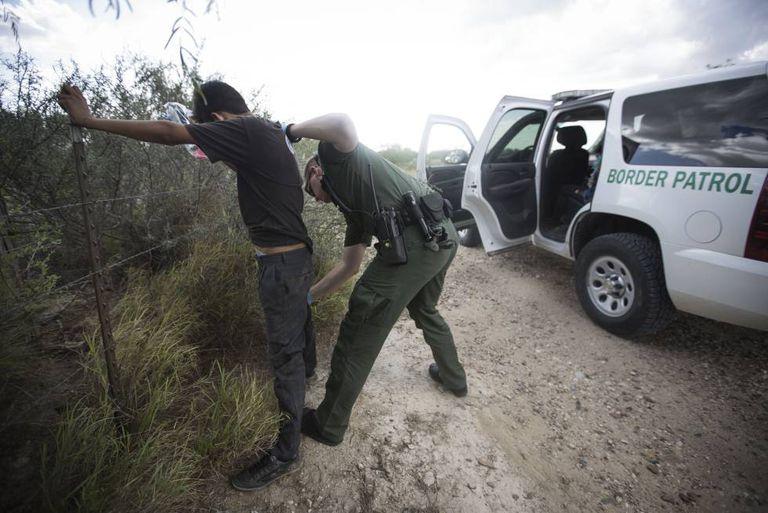 Agente da Polícia de Fronteira revista imigrante sem documentos em Roma, Texas.
