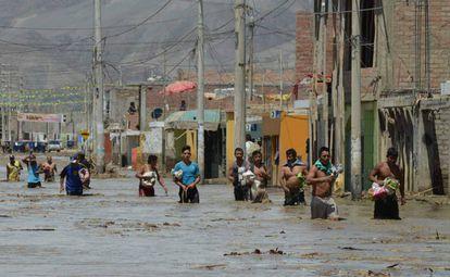 No norte de Lima, moradores caminham na água barrenta.