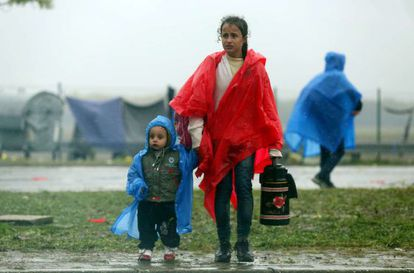 Duas crianças esperam na fronteira entre Croácia e Eslovênia, nesta segunda-feira.