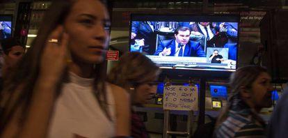 Pessoas passam diante de TV durante votação na Câmara, nesta quarta.