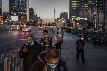 Chineses, todos de máscara, fazem fila no ponto de ônibus em Pequim, em 20 de março.