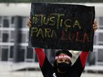 "A demonstrator wearing a mask to curb the spread of the new coronavirus and wearing a headband with text in Portuguese that reads ""Bolsonaro out"" raises a sign that reads ""Justice for Lula,"" in reference to former Brazilian President Luiz Inacio Lula da Silva, during protest commemorating the Supreme Court's decision to suspend proceedings against Lula, in front of the Supreme Court building in Brasilia, Brazil, Monday, March 8, 2021. (AP Photo/Eraldo Peres)"