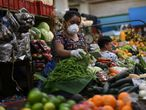 An indigenous woman wears a face mask and gloves as a preventive measure against the new coronavirus, COVID-19, while selling vegetables at Mercado Central in Guatemala City, on March 16, 2020. - Guatemala's President Alejandro Giammattei announced Monday the closure of borders and the suspension of international flights to confront the new coronavirus, after the death of a contagious and the increase of cases. (Photo by Johan ORDONEZ / AFP)