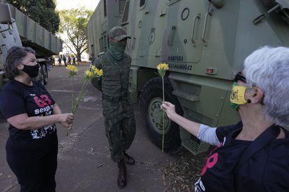 Mulheres entregam flores a militar em dia de desfile de tanques em Brasília, em 10 de agosto.