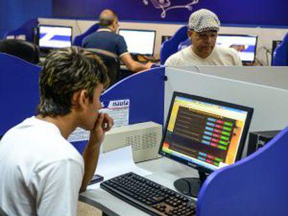 Cubanos se conectam em um cibercafé de Havana.