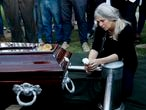 Patricia Nasutti, mother of 18-year-old Ursula Bahillo, who was found in a field stabbed to death on Monday, kneels next to the coffin that contains her daughter's remains at a cemetery during a burial service in Rojas, Argentina, Wednesday, Feb. 10, 2021. Bahillo's ex-boyfriend, a police officer, has been arrested in connection with her death. (AP Photo/Natacha Pisarenko)