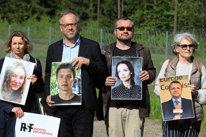 Jornalistas posam na quinta-feira na localidade lituana de Salcininkai com imagens de repórteres bielorrussos detidos.