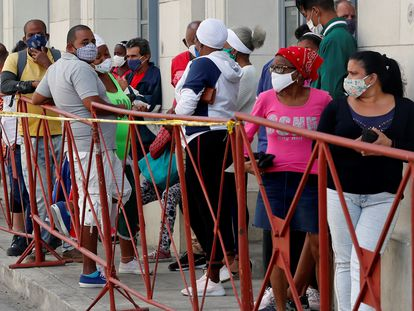 Pessoas de máscara fazem fila para comprar alimentos num mercado de Havana, em fevereiro.
