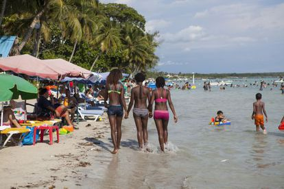Três jovens passeiam pela praia de Boca Chica.