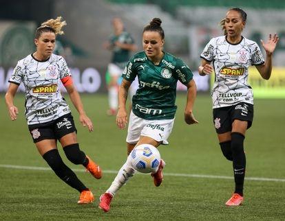 No jogo de ida, Camilinha (Palmeiras) é cercada por Tamires e Adriana (Corinthians).