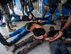 """ACTUALIZA INFORMACIÓN ** AME1213. PUERTO PRÍNCIPE (HAITÍ), 08/07/2021.- Policías custodian hoy a un grupo de sospechosos de haber participado en el asesinato del presidente haitiano, Jovenel Moise, en Puerto Príncipe (Haití). Haití arreció este jueves la operación policial para capturar a los autores del asesinato del presidente Jovenel Moise y anunció la detención de 17 de los 28 supuestos implicados, en su mayoría colombianos. Quince colombianos y dos estadounidenses de origen haitiano están bajo la custodia de la Policía, mientras que otros tres ciudadanos colombianos fueron abatidos en tiroteos con las fuerzas de seguridad, según el primer balance oficial en el que se revela la nacionalidad de los supuestos """"mercenarios"""". EFE/ Jean Marc Hervé Abélard"""