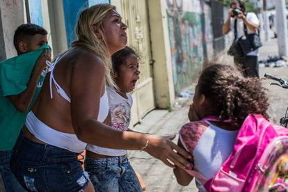 Crianças choram após inalarem gás lacrimogêneo no confronto.