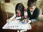 Umas crianças aprendem a fazer contas com um jogo de matemáticas.