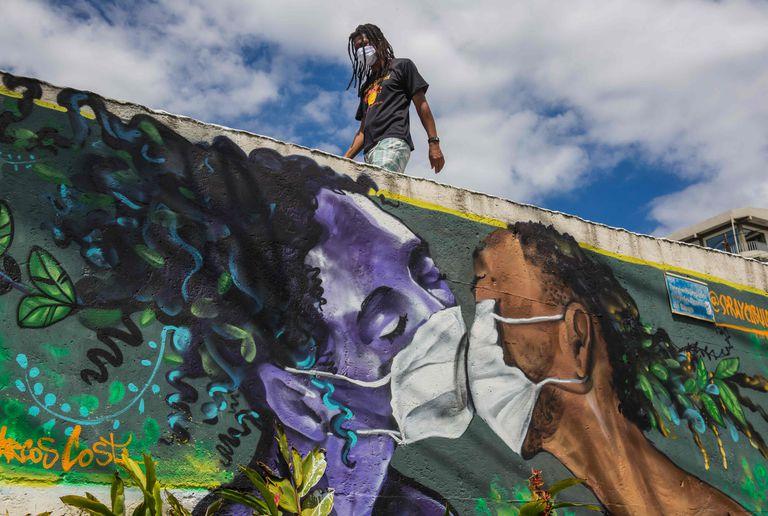 Homem com máscara passa por graffiti de Marcos Costa, o Spray Cabuloso, na entrada da favela Solar de Unhão em Salvador, Bahia, em 15 de abril.
