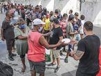 """AME1476. RIO DE JANEIRO (BRASIL), 22/04/2021.- Voluntarios del proyecto """"Covid Sem Fome"""" distribuyen comida a personas pobres el 21 de abril de 2021, en Río de Janeiro (Brasil). Cientos de personas que viven en las calles de Río de Janeiro, o que han terminado allí por culpa de la pandemia, reciben al menos un plato de comida al día en el centro de la ciudad, una cifra muy inferior a la de un año atrás por el desplome en las donaciones. """"Covid sem fome"""", proyecto de voluntarios que surgió en abril del año pasado, cuando Brasil entró en confinamiento total para frenar la propagación del virus, trabaja de sol a sombra para que cada día unas 200 personas, en condiciones de vulnerabilidad, tengan algo que comer. EFE/André Coelho"""