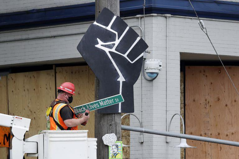 """Funcionário retira placa """"Black Lives Matter St."""" em Seattle, EUA."""