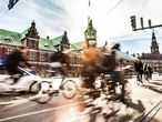 Ciclistas em Copenhague, com o edifício da Bolsa ao fundo