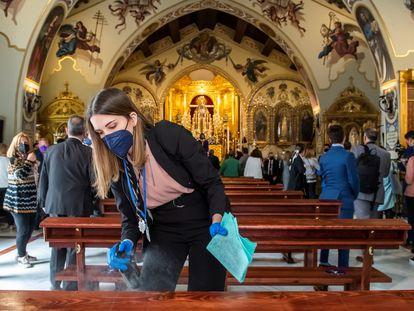 Uma jovem desinfeta os bancos da igreja de Santa Genoveva, em Sevilha (Espanha).