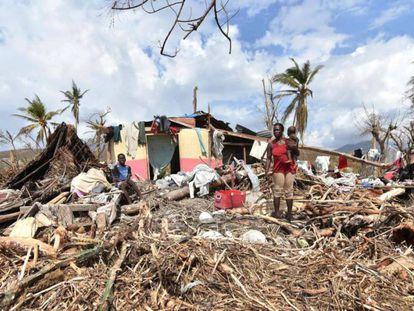 Uma mulher, na segunda-feira em frente à sua casa destruída no Haiti.