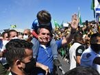 "Brazilian President Jair Bolsonaro carries the son of a supporter on his shoulders as he greets supporters during a demonstration in Brasilia, on May 31, 2020 during the COVID-19 novel coronavirus pandemic. - Bolsonaro, who fears the economic fallout from stay-at-home orders will be worse than the virus, has berated governors and mayors for imposing what he calls ""the tyranny of total quarantine."" Even as his country surpassed France to have the world's fourth-highest death toll, Bolsonaro called for Brazil's football season to resume. (Photo by EVARISTO SA / AFP)"