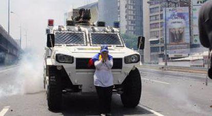 María José Castro caminha com uma bandeira da Venezuela até um blindado da Guarda Nacional Bolivariana
