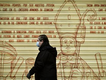 Mulher caminha diante de grafite com mensagens religiosas que pedem proteção em diversas línguas, em Pamplona, na Espanha.