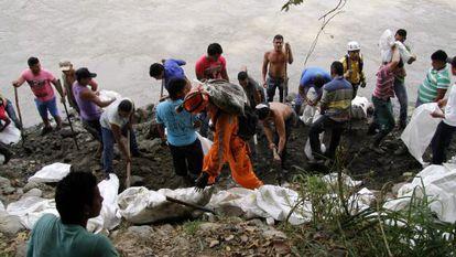 Mineiros escavam à orla do rio Cauca em busca de 15 colegas.