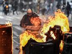 TOPSHOT - A man stands behind a burning barricade during the fifth straight day of protests against police brutality in Bogota on September 13, 2020. - Bogota's Mayor Claudia Lopez, apologized this Sunday for the abuses of the public force, in a ceremony that gathered relatives of the dead and wounded during the bloody protests that broke out five days ago against police brutality in Colombia. (Photo by Juan BARRETO / AFP)