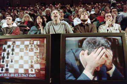 Fãs de xadrez acompanham surpresos o jogo entre a máquina Deep Blue, da IBM, e o campeão do mundo, Gary Kasparov, que aparece desesperado no monitor.
