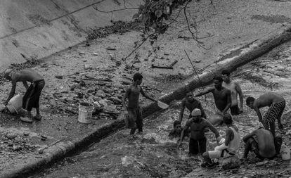 Jovens procuram objetos de valor nas águas do rio Guaire.
