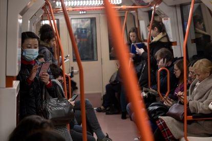 Mulheres no metrô de Madri usando máscaras enquanto olham para o celular.