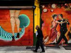 A man wearing a face mask walks past a mural with tango dancers in Buenos Aires, on May 8, 2020 amid the Covid-19 coronavirus pandemic. (Photo by RONALDO SCHEMIDT / AFP)